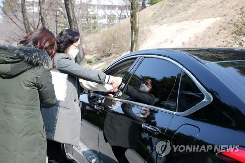 Teachers of Pohang Jecheol Middle School in Pohang, southeast South Korea, distribute textbooks to a parent in a drive-thru on March 19, 2020. (Yonhap)