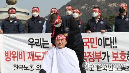 Choe Ung-sik, head of the labor union of South Korean employees for the U.S. Forces Korea, has his head shaved in protest over potential furloughs during a rally in Seoul on March 20, 2020. (Yonhap)
