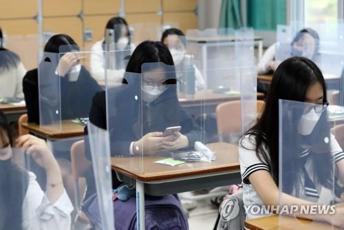 High school seniors sit at desks fitted with plastic dividers in the southern city of Daejeon on May 20, 2020. (Yonhap)
