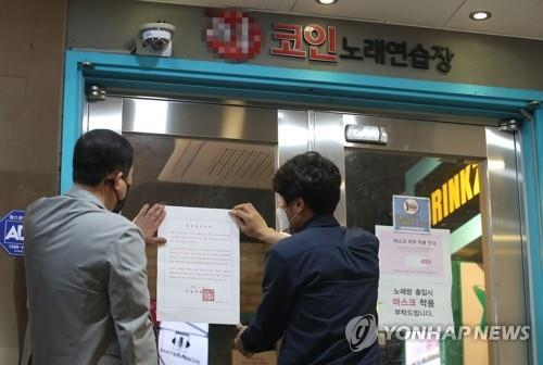 "Seoul city officials put a notice of business suspension on the entrance of a ""coin noraebang,"" a coin-operated karaoke room, in Seoul on May 22, 2020. (Yonhap)"