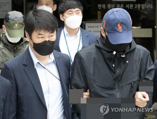 "Two paid members (wearing both masks and caps) of the ""Baksabang"" chatroom on the messaging service Telegram leave the Seoul Central District Court on May 25, 2020, after attending their arrest warrant hearing. (Yonhap)"