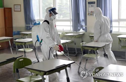 Health care officials disinfect a high school in the southeastern port city of Busan on May 30, 2020, after a third grader was confirmed to have contracted the new coronavirus a day earlier. (Yonhap)