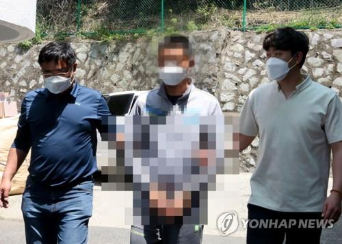 This photo, provided by the Taean Maritime Police Station in the western coastal county of Taean, shows a Chinese national (C) being taken to the police station. He is one of eight Chinese people who sneaked onto the west coast of South Korea via a 1.5-ton motorboat from China on May 21, 2020. (PHOTO NOT FOR SALE) (Yonhap)