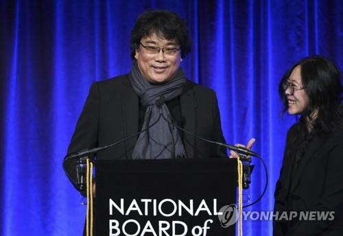 "In this photo released by the Associated Press, South Korean director Bong Joon-ho (L) speaks at the National Board of Review Awards gala in New York for winning the best foreign language film for ""Parasite"" on Jan. 8, 2020. His interpreter Sharon Choi stands next to him. (Yonhap)"