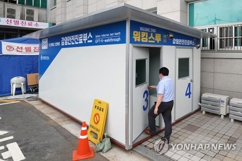 This photo provided by Dongdaemun Ward Office shows a person walking into a walk-thru clinic located in Seoul on July 7, 2020, to be tested for the coronavirus. (Yonhap)