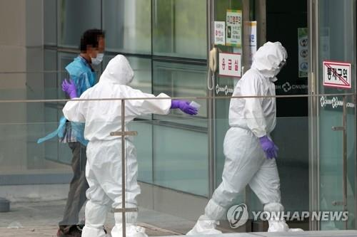 A medical worker takes a man infected with the new coronavirus to a hospital in the southwestern city of Gwangju on July 7, 2020. Police officers took the man in his 60s into custody at a construction site in the nearby town of Yeonggwang after he went into hiding with his smartphone turned off. (Yonhap)