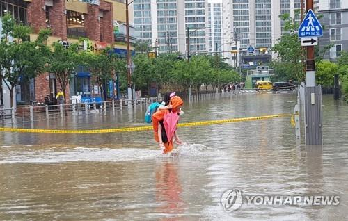 A firefighter carrying a young girl on his back crosses a flooded road in Busan on July 10, 2020, after heavy rainfall in the southern port city, in this photo provided by the Busan Metropolitan City Fire Disaster Headquarters. (PHOTO NOT FOR SALE) (Yonhap)