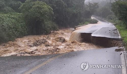 This photo, provided by the National Fire Agency, shows a collapsed road in Chungju, North Chungcheong Province, which left one firefighter missing, on Aug. 2, 2020. (PHOTO NOT FOR SALE) (Yonhap)