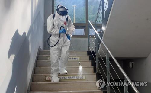 A health worker disinfects a stairway at a high school in Busan on Aug. 13, 2020. (Yonhap)