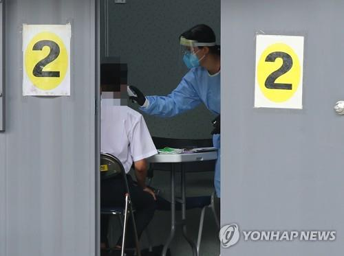 A health worker checks the body temperature of a citizen at a virus screening clinic in Seoul on Aug. 18, 2020. (Yonhap)