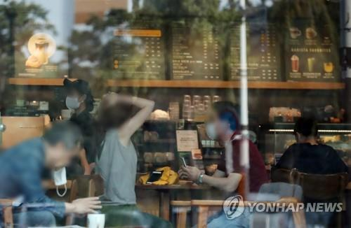 Customers drink coffee and spend time inside a franchise coffee shop in downtown Seoul on Sept. 14, 2020, after the government relaxed social distancing measures. (Yonhap)