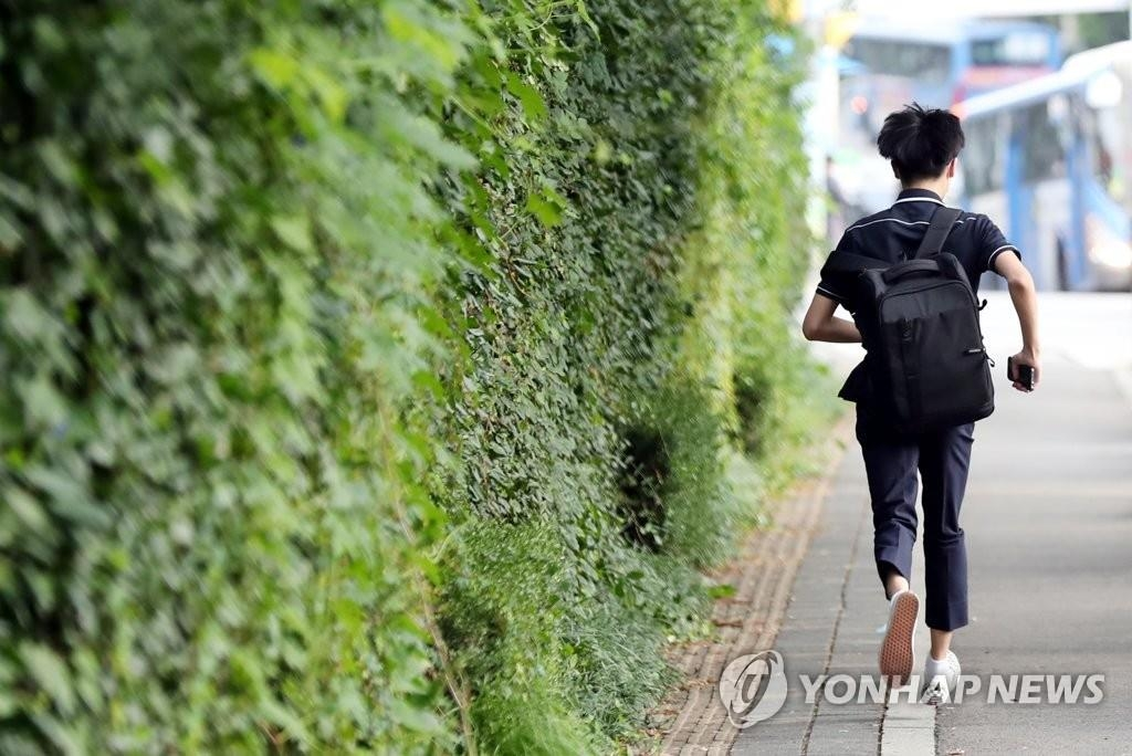 A student runs toward his school in Incheon, South Korea, on Sept. 21, 2020, as his school reopened after about a month amid a slowdown in new coronavirus cases. (Yonhap)