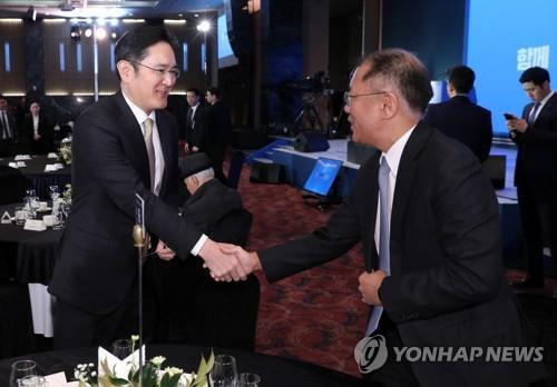 Samsung Group Vice Chairman Lee Jae-yong (L) shakes hands with Hyundai Motor Group Executive Vice Chairman Chung Euisun at a meeting for the new year in Seoul on Jan. 2, 2020. (Yonhap)
