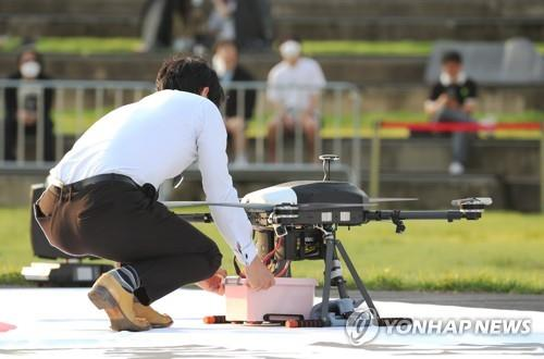 This photo taken on Sept. 19, 2020, shows a person receiving a food box delivery from a drone during a government-led test event in the administrative city of Sejong, some 130 kilometers southeast of Seoul. (Yonhap)