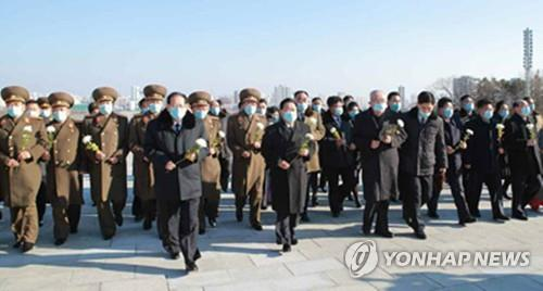 This image, captured from North Korea's Rodong Sinmun newspaper on Jan. 17, 2021, shows Choe Ryong-hae, the president of the Presidium of the Supreme People's Assembly, and parliamentary representatives walking toward statues of former North Korean leaders in Pyongyang to offer flowers. (PHOTO NOT FOR SALE) (Yonhap)