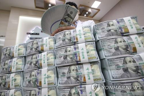 In the file photo, a bank official inspects U.S. dollars before their release at a Seoul branch of Hana Bank. (Yonhap)