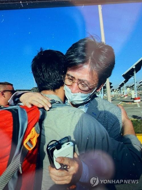 Minister Counselor Kim Il-eung of the South Korean Embassy in Kabul hugs an Afghan as he leads an evacuation mission, in this undated photo, released on Aug. 25, 2021, by the foreign ministry. (PHOTO NOT FOR SALE) (Yonhap)