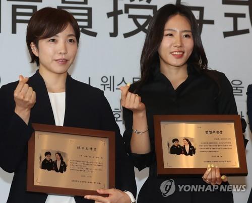 「韓日友情賞」を受け取った李(右)と小平=7日、ソウル(聯合ニュース)
