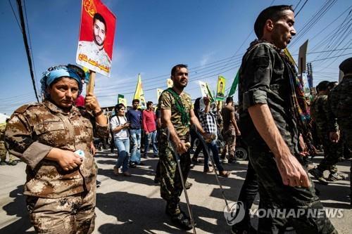 이달 8일(현지시간) 시리아에 있는 유엔 사무소 앞에서 민병대 참전 병사들과 퇴역 병사들이 터키의 쿠르드 공격을 규탄하며 행진하고 있다. [AFP=연합뉴스]