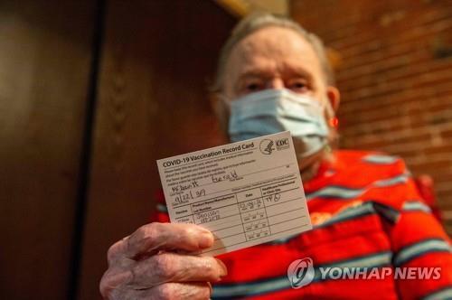 백신 접종 증명서를 들어보이는 미 노인[AFP=연합뉴스]