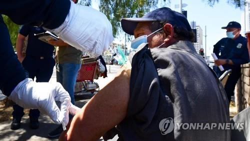 미 캘리포니아 LA소방서의 코로나19 아웃리치팀이 14일(현지시간) 노숙인들에게 코로나19 백신을 접종하고 있다. [AFP=연합뉴스]