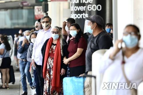 19일(현지시간) 실내 마스크 착용이 다시 의무화된 미국 LA의 LA국제공항에 마스크를 쓴 여행객들이 서 있다. [신화=연합뉴스]