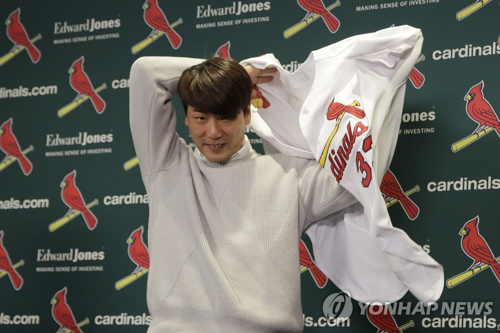 In this Associated Press photo, South Korean pitcher Kim Kwang-hyun puts on a new St. Louis Cardinals jersey during a press conference at Busch Stadium in St. Louis on Dec. 17, 2019. (Yonhap)