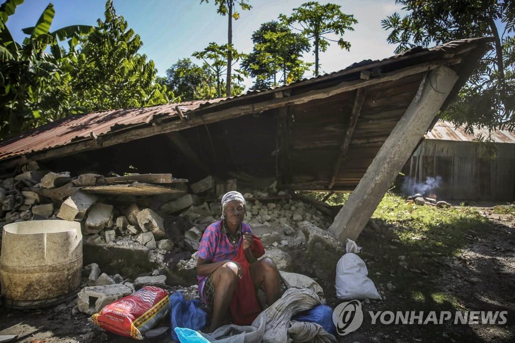 지진으로 무너진 집 앞에 앉아있는 아이티 레카이 주민