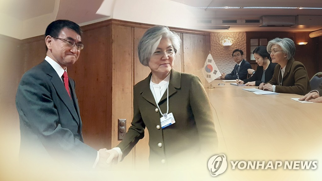This image, provided by Yonhap News TV, shows Foreign Minister Kang Kyung-wha (2nd from L) shaking hands with her Japanese counterpart, Taro Kono. (Yonhap)