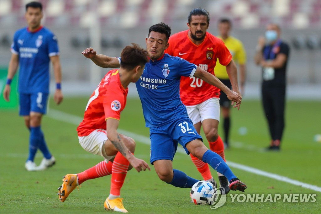 In this AFP photo, Lee Ki-je of Suwon Samsung Bluewings (C) tries to dribble past Yang Liyu of Guangzhou Evergrande (L) during their Group G match at the Asian Football Confederation Champions League at Khalifa International Stadium in Doha on Nov. 22, 2020. (Yonhap)