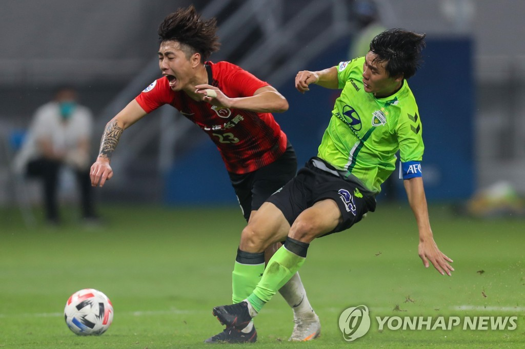 In this AFP photo, Choi Chul-soon of Jeonbuk Hyundai Motors (R) battles Fu Huan of Shanghai SIPG during their Group H match at the Asian Football Confederation Champions League at Khalifa International Stadium in Doha on Nov. 22, 2020. (Yonhap)