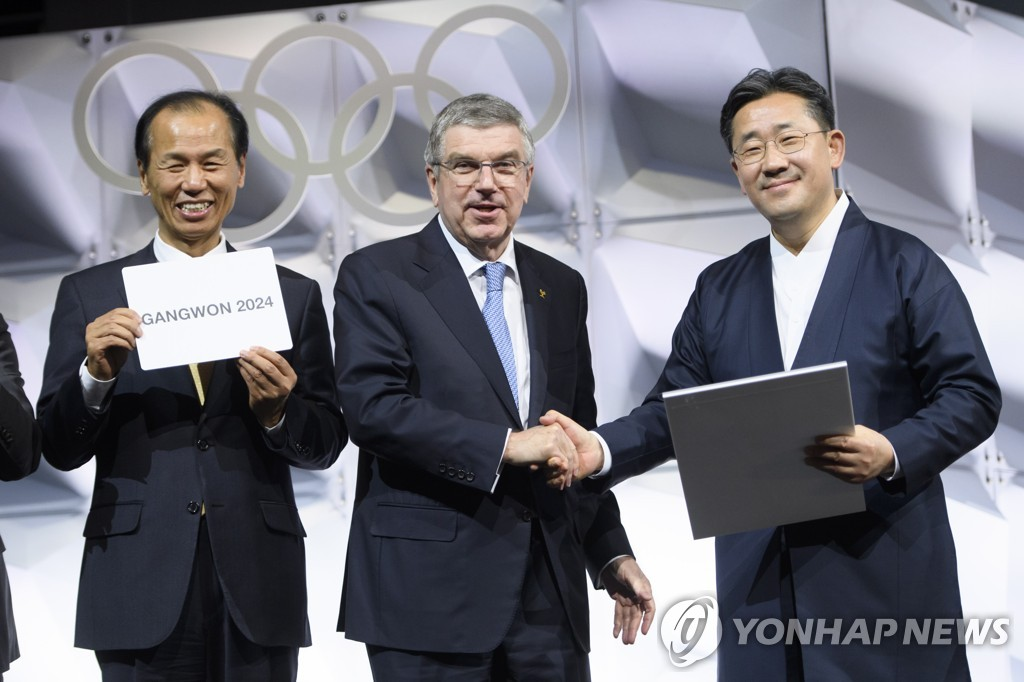 In this EPA file photo from Jan. 10, 2020, Choi Moon-soon (L), governor of South Korea's Gangwon Province, holds a card showing the name of Gangwon Province of South Korea as the host of the 2024 Winter Youth Olympics, following an election at the 135th International Olympic Committee (IOC) Session in Lausanne, Switzerland. Others with Lee are Thomas Bach (C), president of the IOC, and Park Yang-woo, South Korean minister of culture, sports and tourism. (Yonhap)