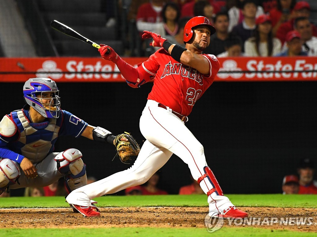 In this Getty Images file photo from Sept. 12, 2018, Jose Miguel Fernandez (R), then of the Los Angeles Angels, hits a two-run home run against the Texas Rangers in the bottom of the third inning of a Major League Baseball regular season game at Angel Stadium in Anaheim, California. (Yonhap)