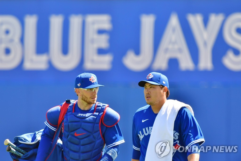 In this Getty Images file photo from March 5, 2021, Toronto Blue Jays' pitcher Ryu Hyun-jin (R) and his catcher, Danny Jansen, walk out to the field at TD Ballpark in Dunedin, Florida, before a major league spring training game against the Baltimore Orioles. (Yonhap)
