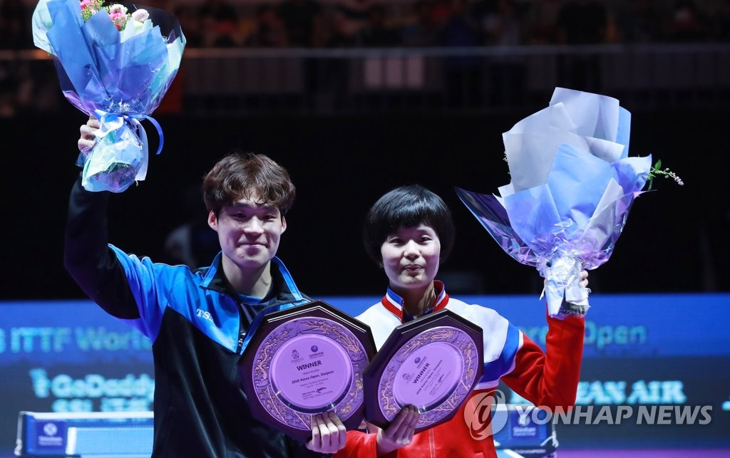 In this file photo from July 21, 2018, Jang Woo-jin of South Korea (L) and Cha Hyo-sim of North Korea pose with the champions' trophy after winning the gold medal in the mixed doubles at the International Table Tennis Federation (ITTF) World Tour Platinum Korea Open at Chungmu Sports Arena in Daejeon, 160 kilometers south of Seoul. (Yonhap)