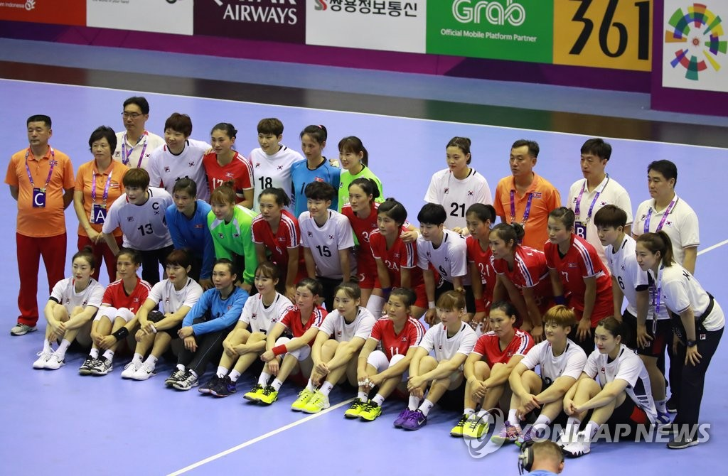 In this file photo from Aug. 14, 2018, members of the South Korean and North Korean women's handball teams pose for photos together before the start of their preliminary match at the Asian Games at GOR Popki Cibubur in Jakarta. (Yonhap)