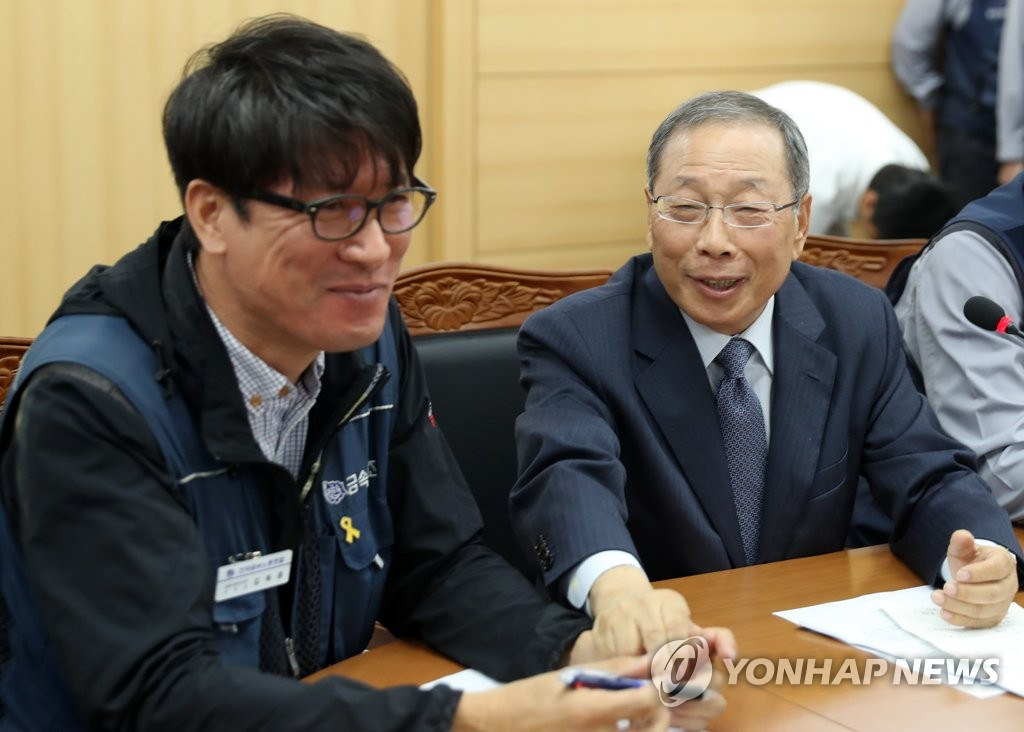 In this photo, taken Sept. 14, 2018, SsangYong Motor CEO Choi Jong-sik (R) holds hand of Kim Deuk-joong, chief of SsangYong Motor branch of the Korean Metal Workers' Union, after signing an agreement to rehire 119 fired workers by 2019. (Yonhap)