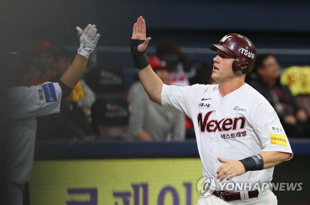 In this file photo from Oct. 16, 2018, Jerry Sands of the Nexen Heroes (R) high-fives a teammate after scoring a run against the Kia Tigers in the bottom of the fifth inning of a Korea Baseball Organization wild card game at Gocheok Sky Dome in Seoul. (Yonhap)