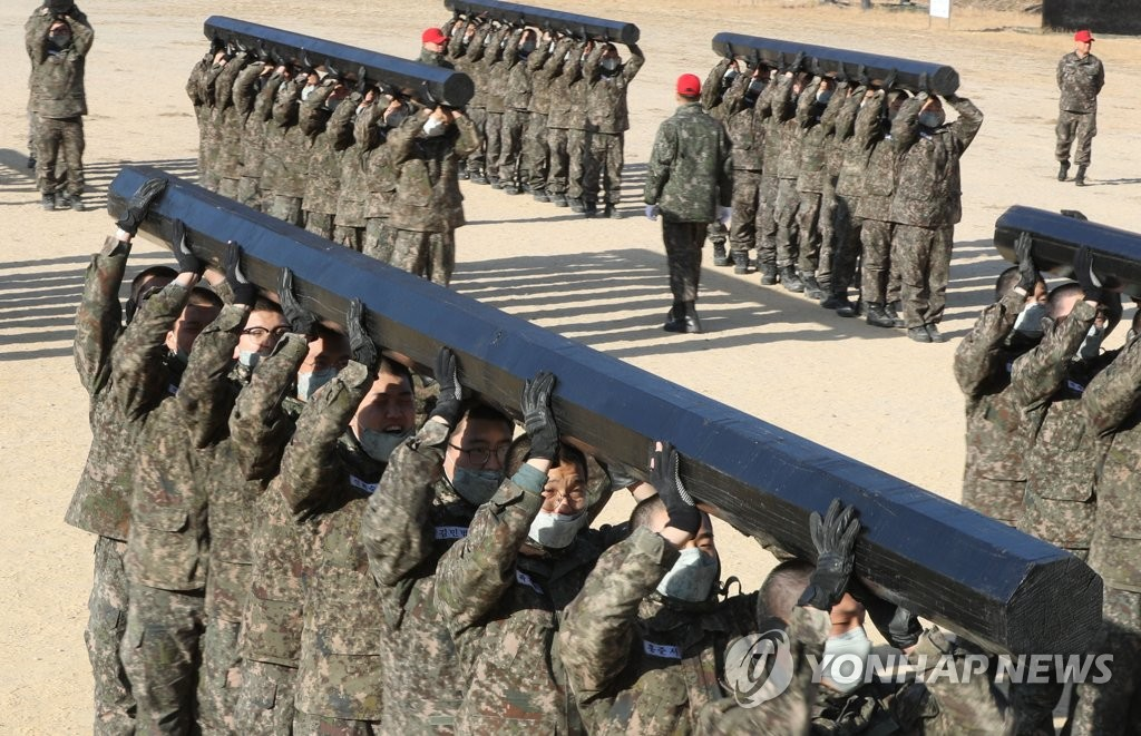 In this file photo taken on Jan. 29, 2019, a group of recruits executes log curls as a team during a training session at a Navy boot camp in the southwestern port city of Changwon. All able-bodied South Korean men are required to serve almost two years in the military. (Yonhap)