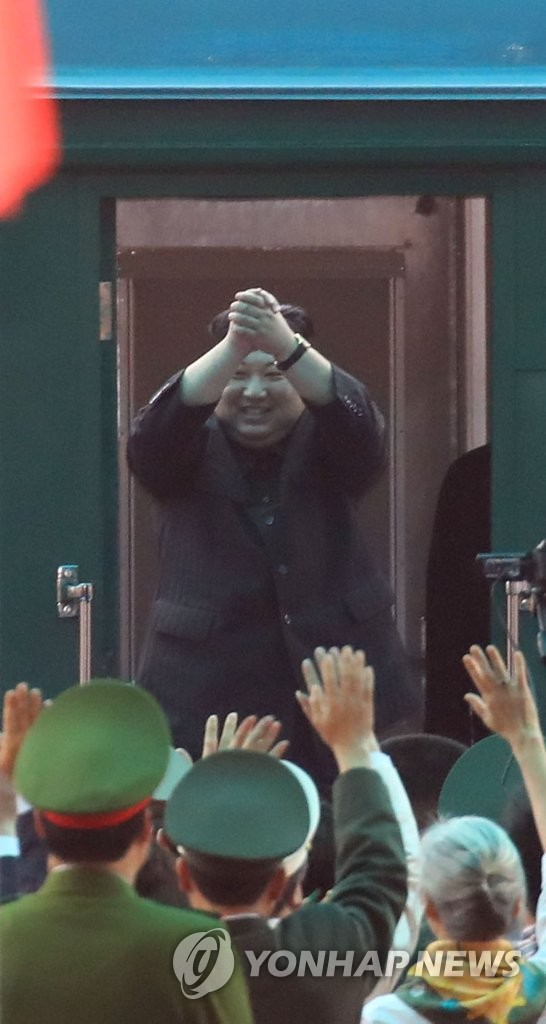 North Korean leader Kim Jong-un raises his hands in greeting before departing from a train station in the Vietnamese border town of Dong Dang on March 2, 2019, after his five-day visit to the Southeast Asian country. (Yonhap)