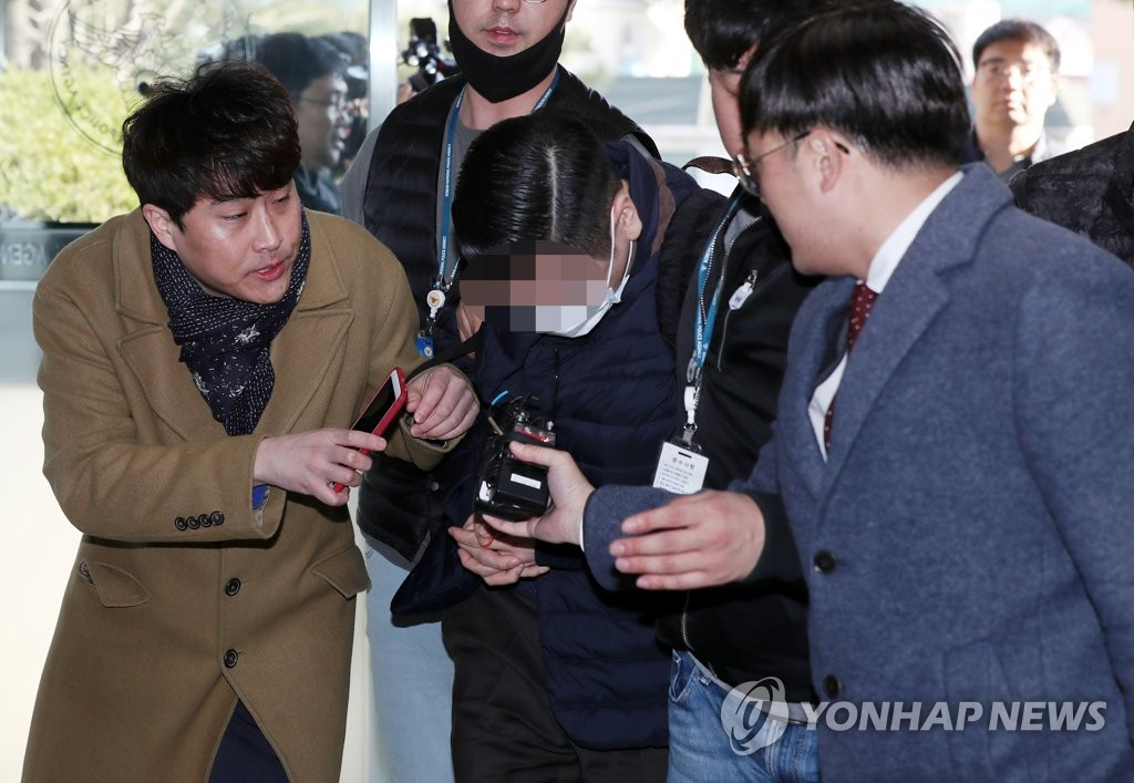 Wearing a face mask, a grandson of SK Group founder appears at a police station on April 1, 2019, after he was arrested for allegedly purchasing liquid marijuana. (Yonhap)