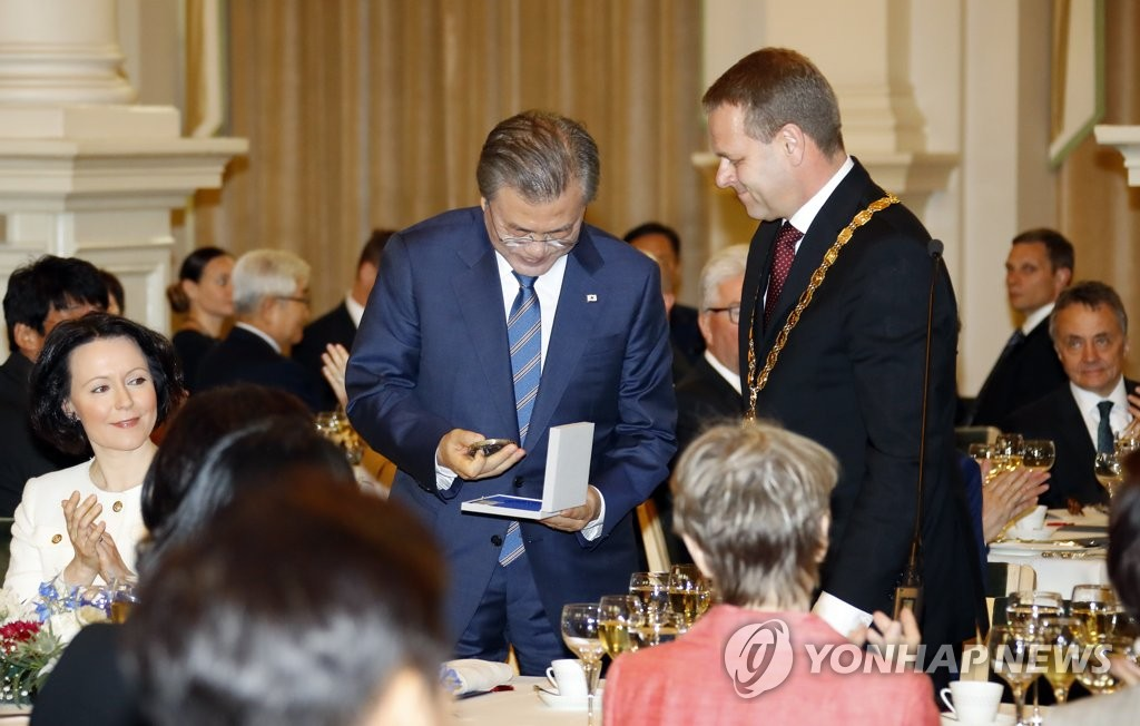South Korean President Moon Jae-in receives a commemorative medal from Helsinki Mayor Jan Vapaavuori at the City Hall of the Finnish capital on June 10, 2019. (Yonhap)