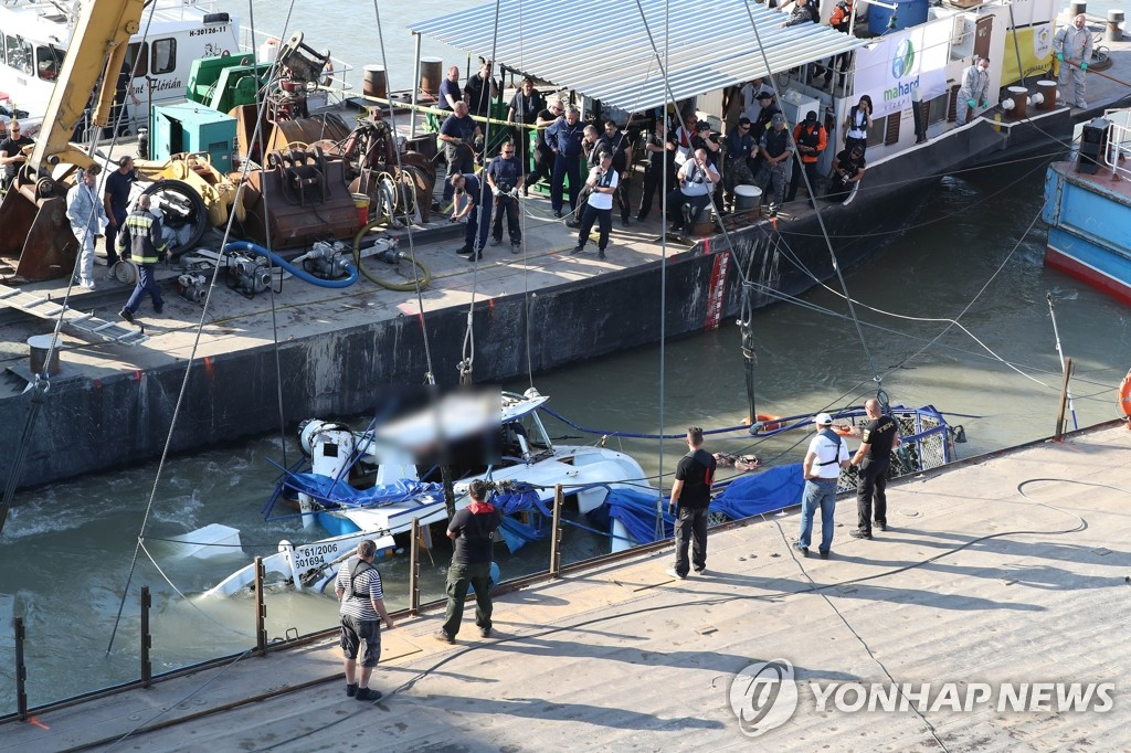 The Hableany, a tour boat that sank in Hungary in a deadly accident that left 26 South Koreans dead or missing, is lifted by Hungarian authorities on June 11, 2019, almost two weeks after the tragedy. (Yonhap)