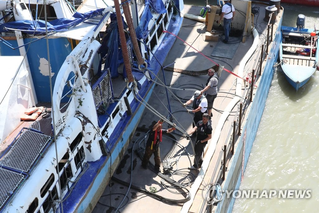 Hungarian workers undo the wires used in the salvaging of the Hableany tour boat raised from the Danube River in Budapest the previous day, nearly two weeks after the deadly sinking that left 22 South Koreans dead and four missing, in this photo taken June 11, 2019. (Yonhap)