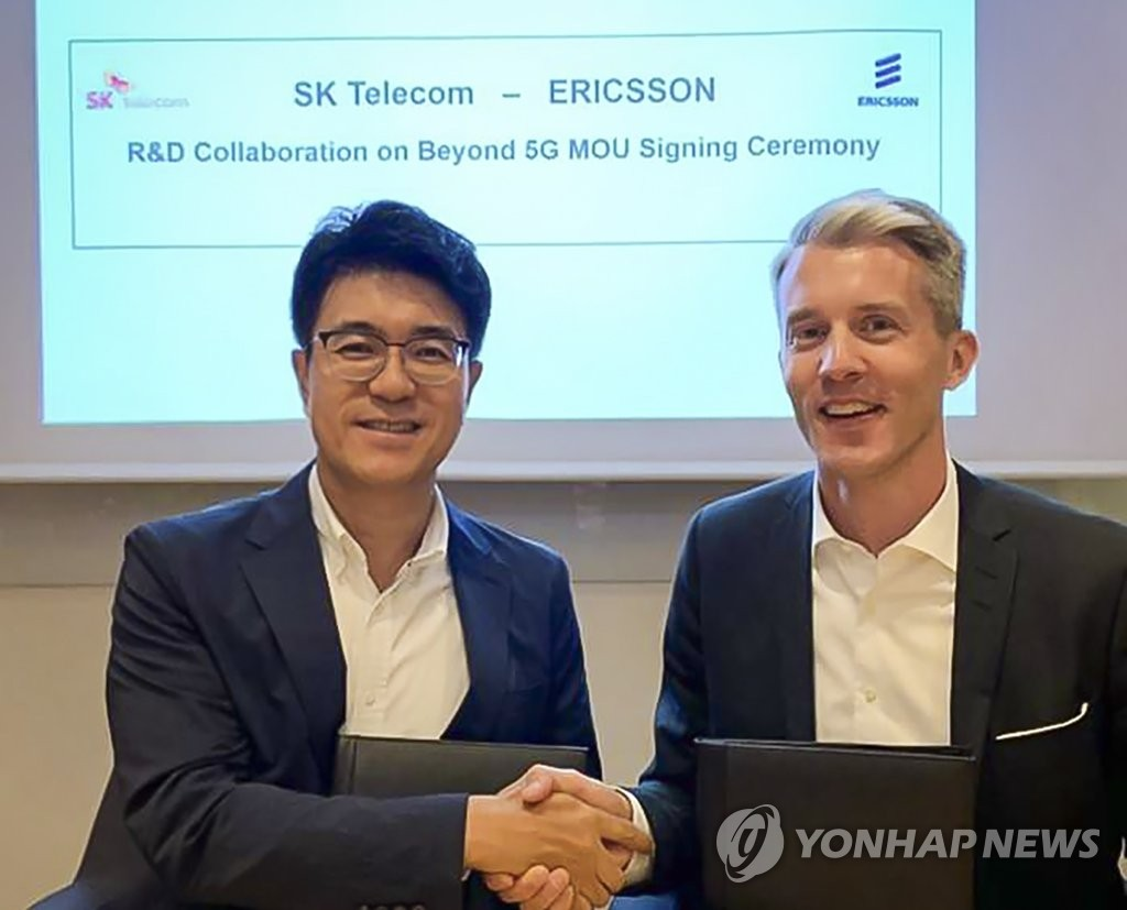 Park Jin-hyo (L), the chief technology officer of SK Telecom Co., shakes hands with Per Narvinger (R), head of product area networks of Ericsson, after signing a memorandum of understanding on R&D collaboration on 5G and 6G during a ceremony held at Ericsson's headquarters in Stockholm, Sweden, on June 13, 2019, in this photo provided by SK Telecom. (PHOTO NOT FOR SALE) (Yonhap)