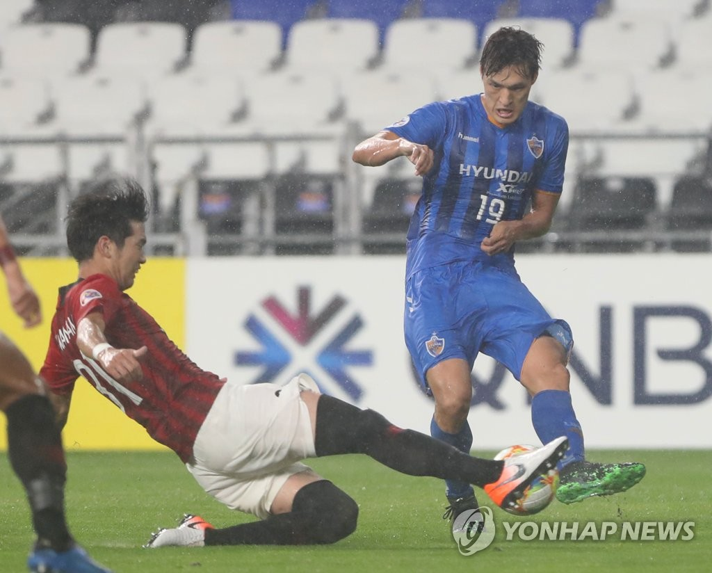 Park Yong-woo of Ulsan Hyundai (R) is tackled by Takuya Iwanami of Urawa Red Diamonds during the second leg of the round of 16 at the Asian Football Confederation Champions League at Munsu Football Stadium in Ulsan, 400 kilometers southeast of Seoul, on June 26, 2019. (Yonhap)