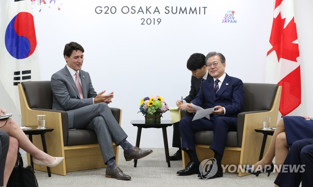 South Korean President Moon Jae-in (R) talks with Canadian Prime Minister Justin Trudeau in Osaka, Japan, on June 29, 2020, on the sidelines of the G-20 summit. (Yonhap)
