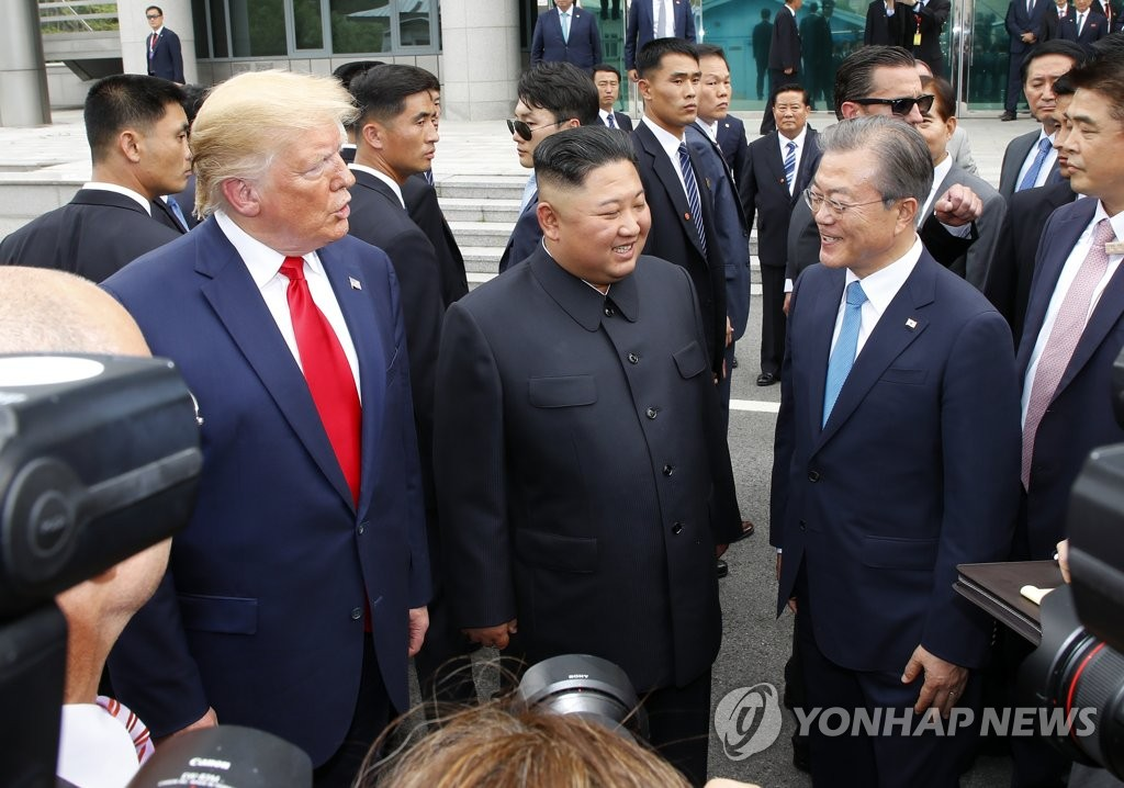 South Korean President Moon Jae-in (R), North Korean leader Kim Jong-un (C), and U.S. President Donald Trump converse in the border village of Panmunjom in the Demilitarized Zone that separates the two Koreas on June 30, 2019. (Yonhap)