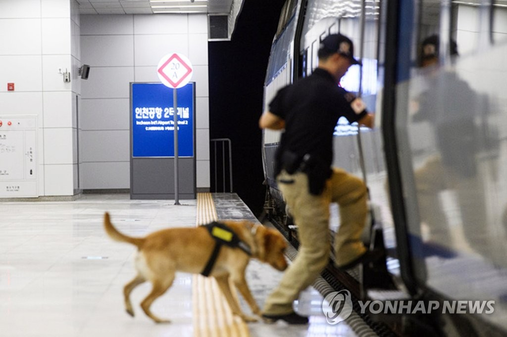 A sniffer dogs hops on to a train with a security guard at the train station that serves Incheon International Airport, west of Seoul, in this file photo provided by Korea Railroad Corp. on July 12, 2019. (PHOTO NOT FOR SALE) (Yonhap)