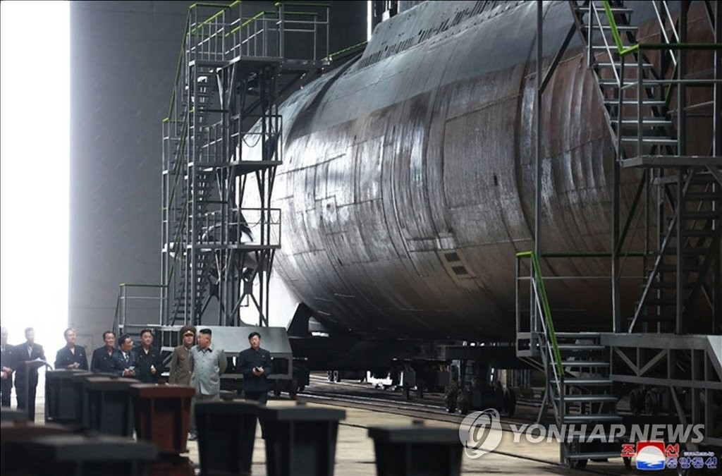 In this photo, released by the Korean Central News Agency on July 23, 2019, North Korean leader Kim Jong-un (2nd from R) inspects a newly built submarine. (For Use Only in the Republic of Korea. No Redistribution) (Yonhap)